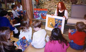 Phoebe Stone showing her artwork to a group of children